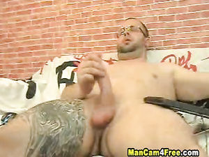 Hunk in glasses enjoys jerking off his dick on gay porn